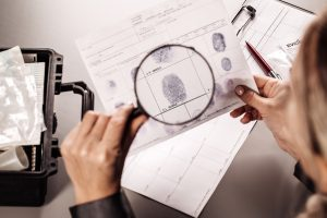 Criminology expert looking through a magnifying glass at a fingerprint