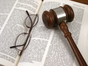 Glasses and gavel on top of open law book