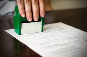 Male hand pressing rubber stamp on document