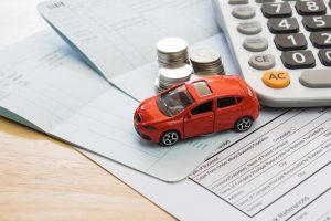 Toy car on desk with papers, calculator, and coins